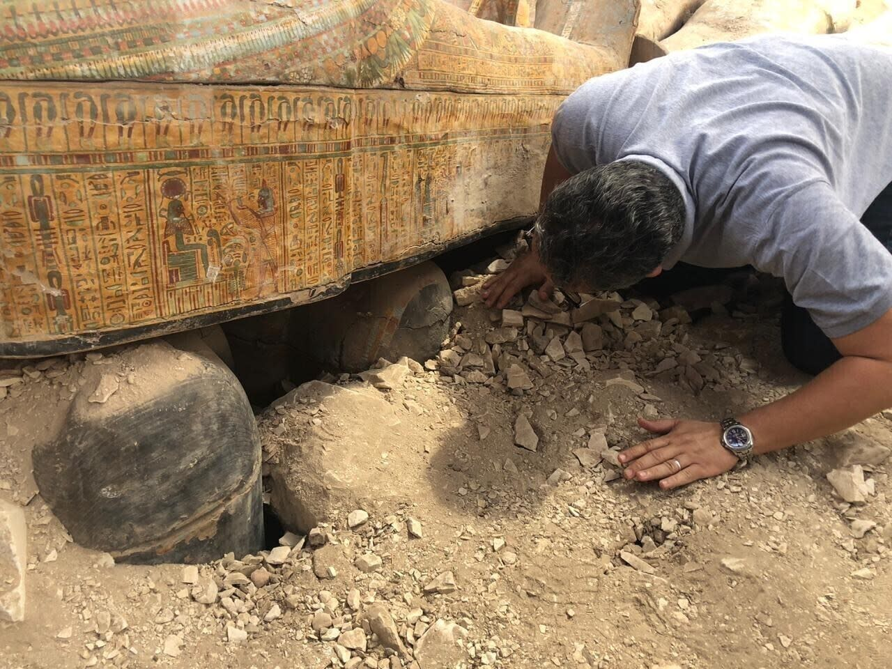 FILE - This Tuesday, Oct. 15, 2019 file photo provided by the Egyptian Ministry of Antiquities shows Egyptian Minister of Antiquities Khaled el-Anany looking at recently discovered ancient colored coffins with inscriptions and paintings, in the southern city of Luxor, Egypt. (Egyptian Ministry of Antiquities via AP, File)