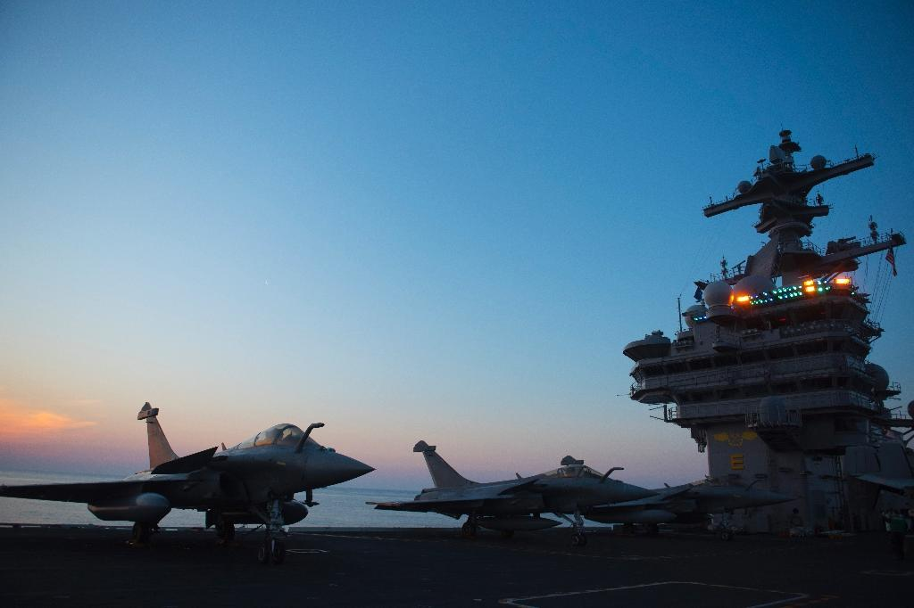 A French Navy Rafale jet is seen early in the morning on the deck of the USS George H.W. Bush aircraft carrier where French crews are honing their skills, in the Atlantic Ocean (AFP Photo/Eric BARADAT)