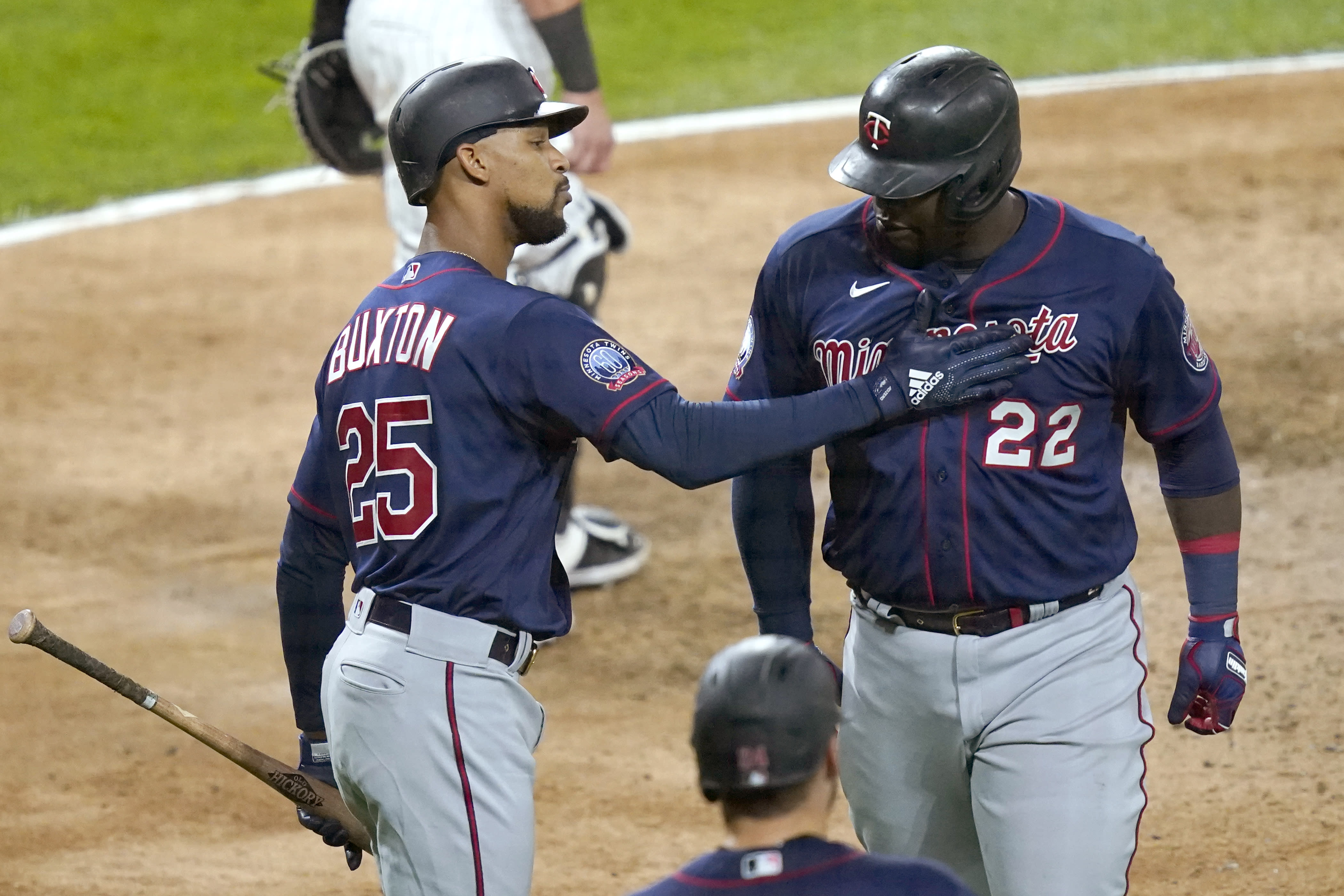 Minnesota Twins' Byron Buxton (25) greets Miguel Sano at home after Sano's two-run home run off Chicago White Sox relief pitcher Matt Foster during the eighth inning of a baseball game Wednesday, Sept. 16, 2020, in Chicago. Josh Donaldson scored on the homer. (AP Photo/Charles Rex Arbogast)