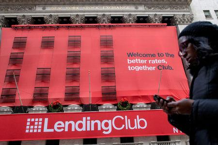 FILE PHOTO: A woman looks at her phone as she passes by a Lending Club banner on the facade of the the New York Stock Exchange December 11, 2014. REUTERS/Brendan McDermid/File Photo
