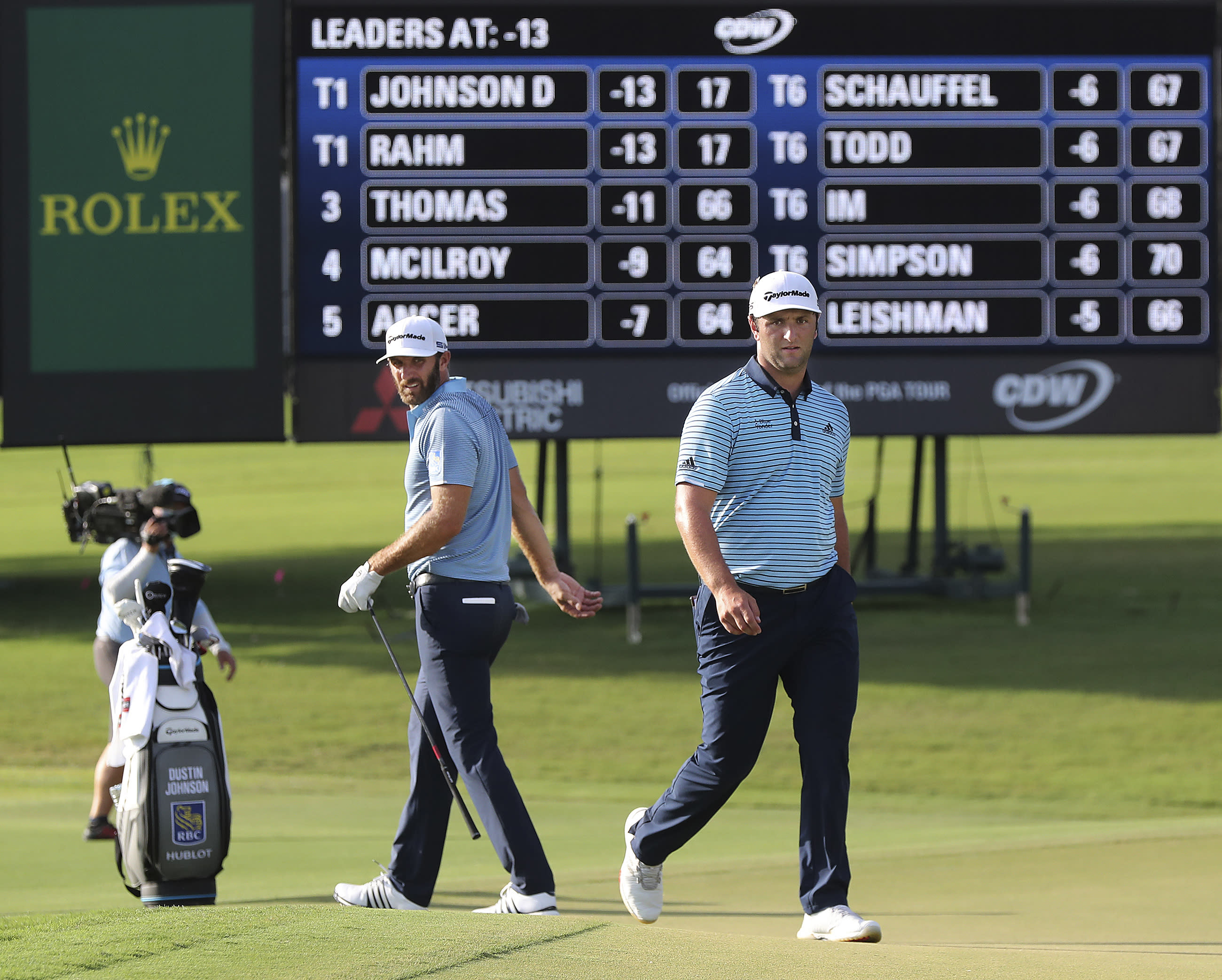 Dustin Johnson, left, and Jon Rahm check out their shots on the 18th green during the first round of the Tour Championship golf tournament at East Lake Golf Club on Friday, Sept. 4, 2020, in Atlanta. (Curtis Compton/Atlanta Journal-Constitution via AP)