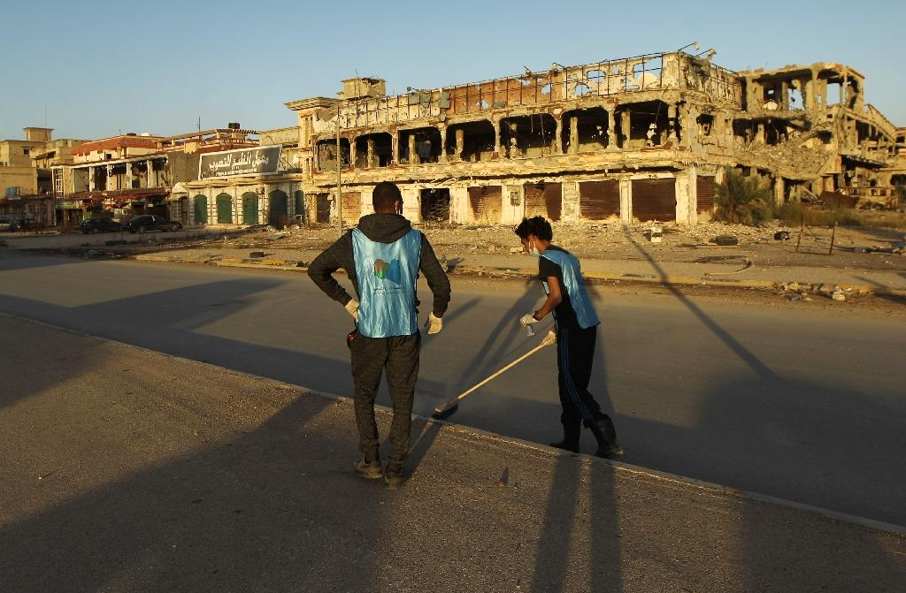Workers in front of destroyed buildings in Laithi district, a central area recently recaptured by forces loyal to Libya's internationally recognised government in Benghazi (AFP Photo/Abdullah Doma)