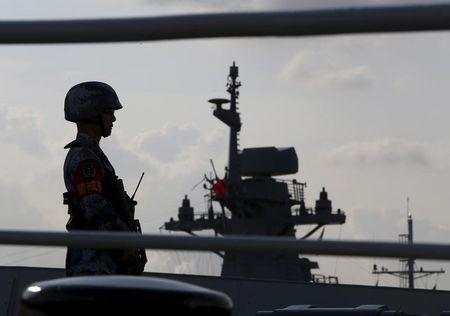 PLA navy personnel stands guard on CNS Yulin during a display of warships ahead of the IMDEX Asia maritime defence exhibition at Changi Naval Base in Singapore