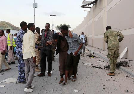 People help a woman injured by a blast near the Mogadishu sea port in Mogadishu, Somalia, May 24, 2017. REUTERS/Feisal Omar