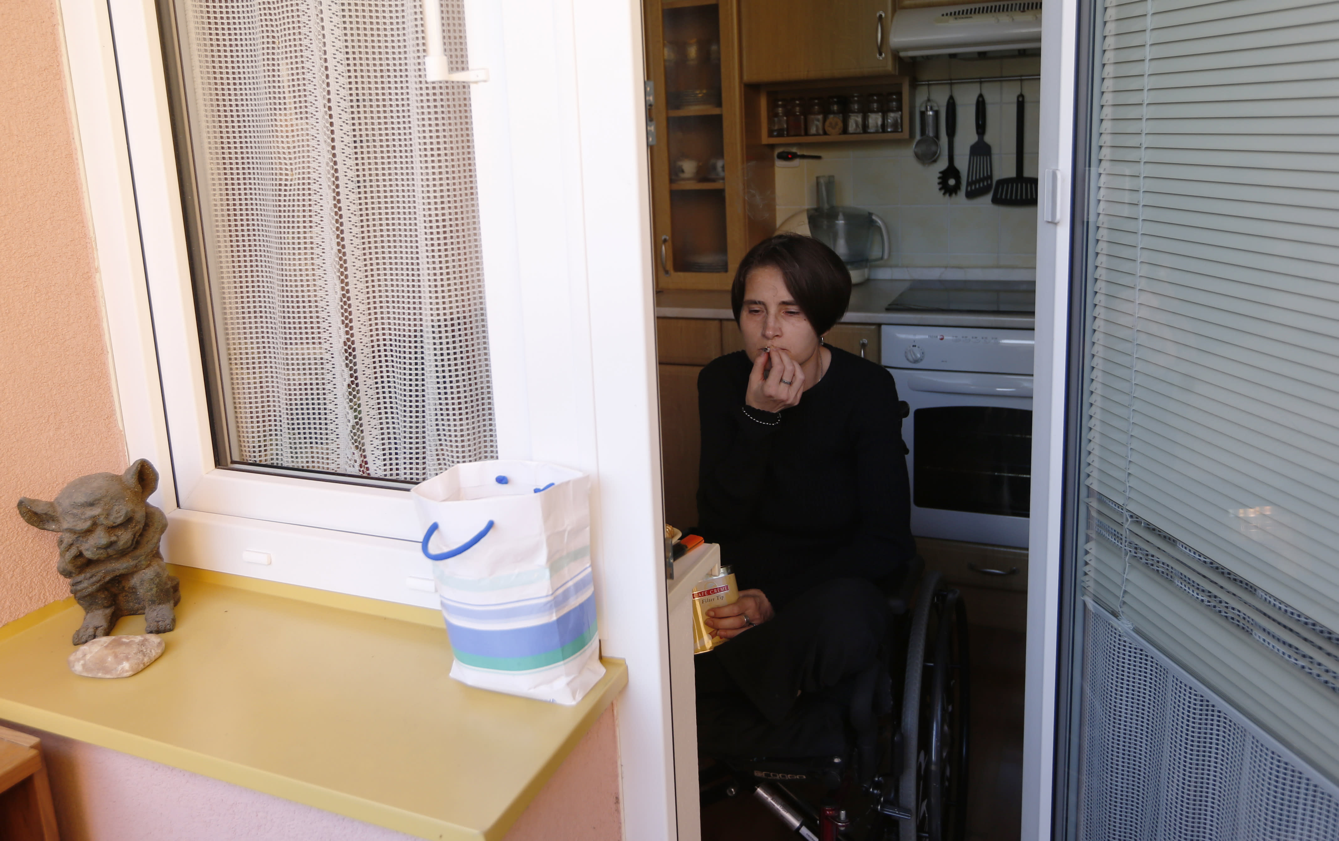 In this Monday, Oct. 14, 2013 photo, Martina Kafkova, a patient diagnosed with multiple sclerosis, smokes a joint at her home in Tyn nad Vltavou, Czech Republic. Confined to a wheelchair, the former non-smoker needs five short joints a day to get relief from severe stiffness, painful spasms and breathing troubles because other available medicine is not effective enough to help. Czech Republic has approved legislation for use of medical marijuana but it is still impossible to obtain it legally. (AP Photo/Petr David Josek)