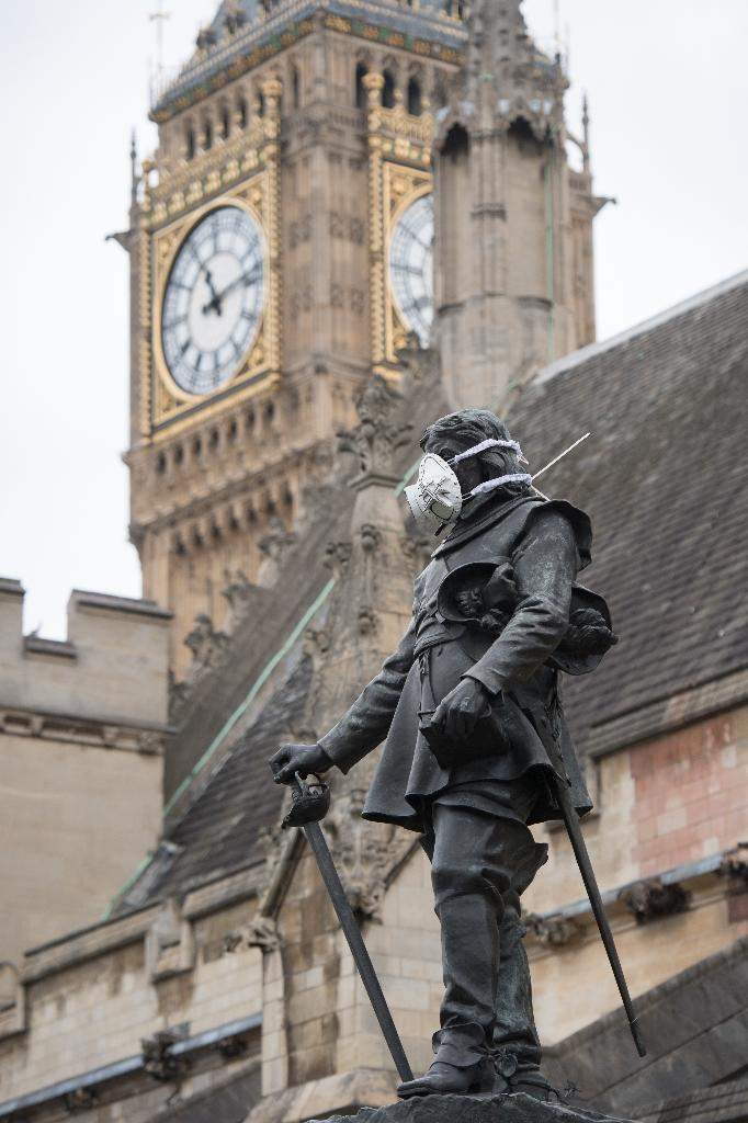 A breathing mask is fixed to a statue of Oliver Cromwell outside the Houses of Parliament in central London on April 18, 2016 (AFP Photo/Leon Neal)