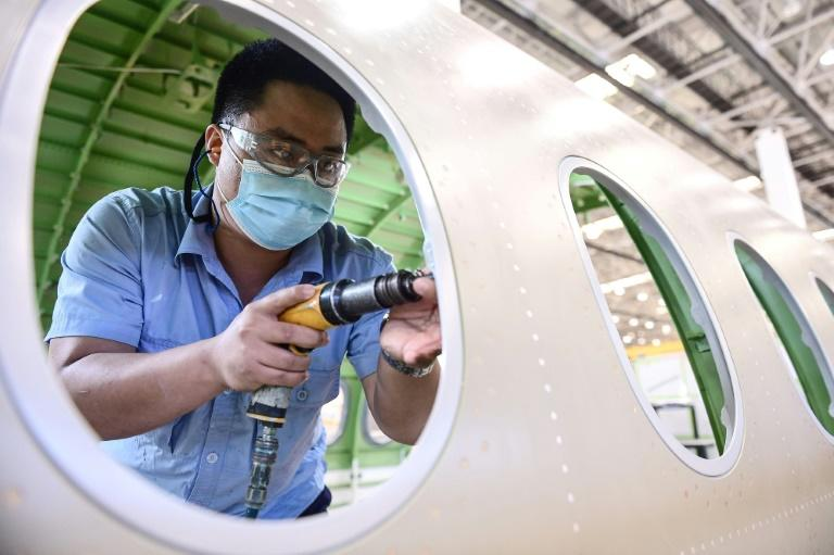 An employee works on an Airbus A220 aircraft at a factory in Shenyang in China's northeast