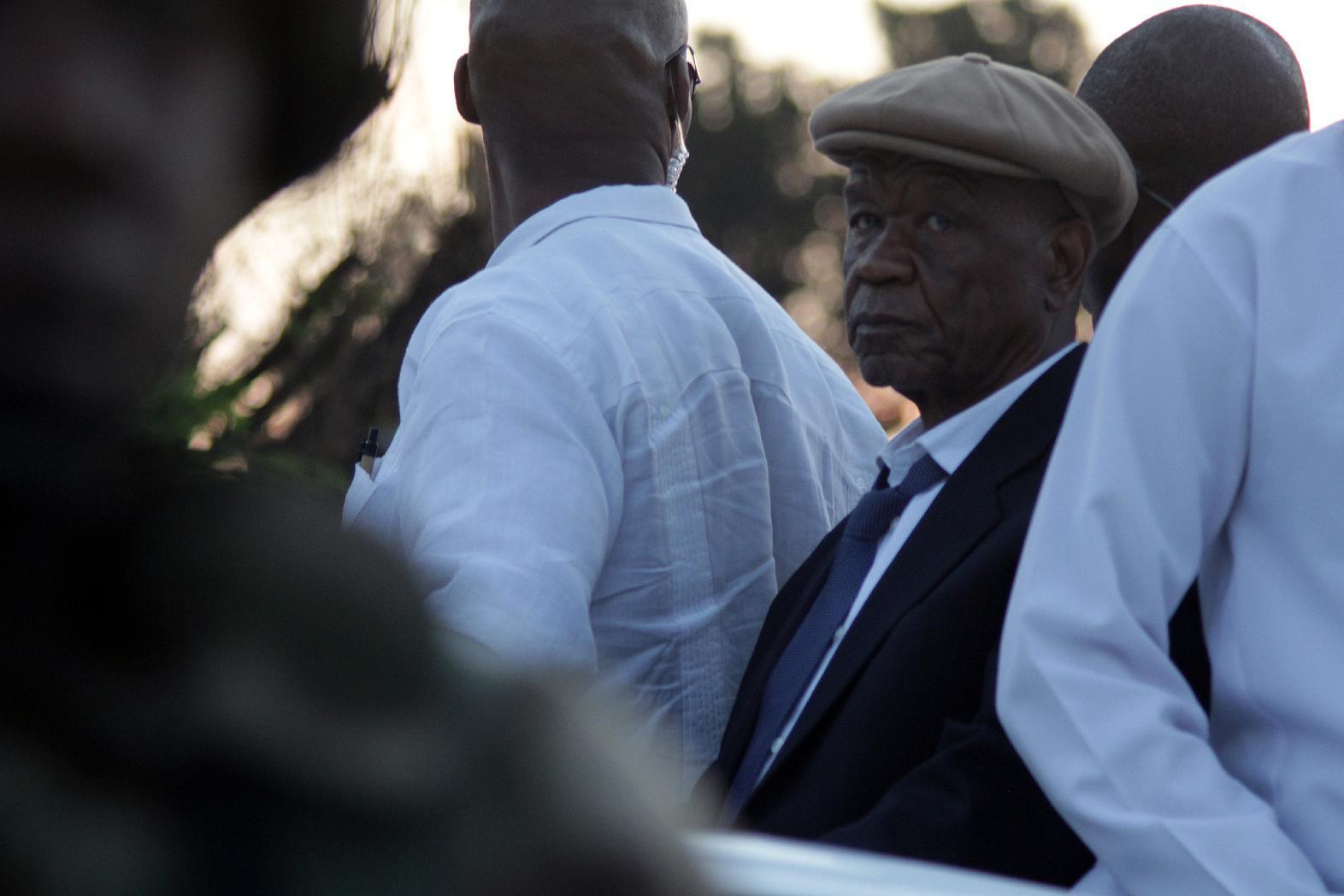 Lesotho Prime Minister Tom Thabane is flanked by his bodyguards as he arrives at the Maseru border gate under heavy security on September 16, 2014 (AFP Photo/Hlompho Letsielo)