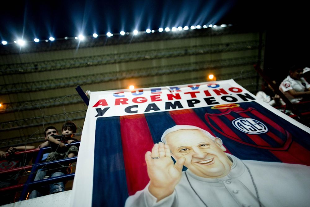 "A banner with an image of Pope Francis and a message that reads in Spanish: ""Cuervo, Argentine and Champion,"" hangs from the stands during a national soccer league match between San Lorenzo and Colon de Santa Fe in Buenos Aires, Argentina, Saturday, March 15, 2014. The San Lorenzo football club launched a special edition team jersey to mark the first anniversary of Pope Francis's election as pontiff, who is a huge fan. The jersey features an  image of Francis with a message that reads in Spanish; ""Happy anniversary."""