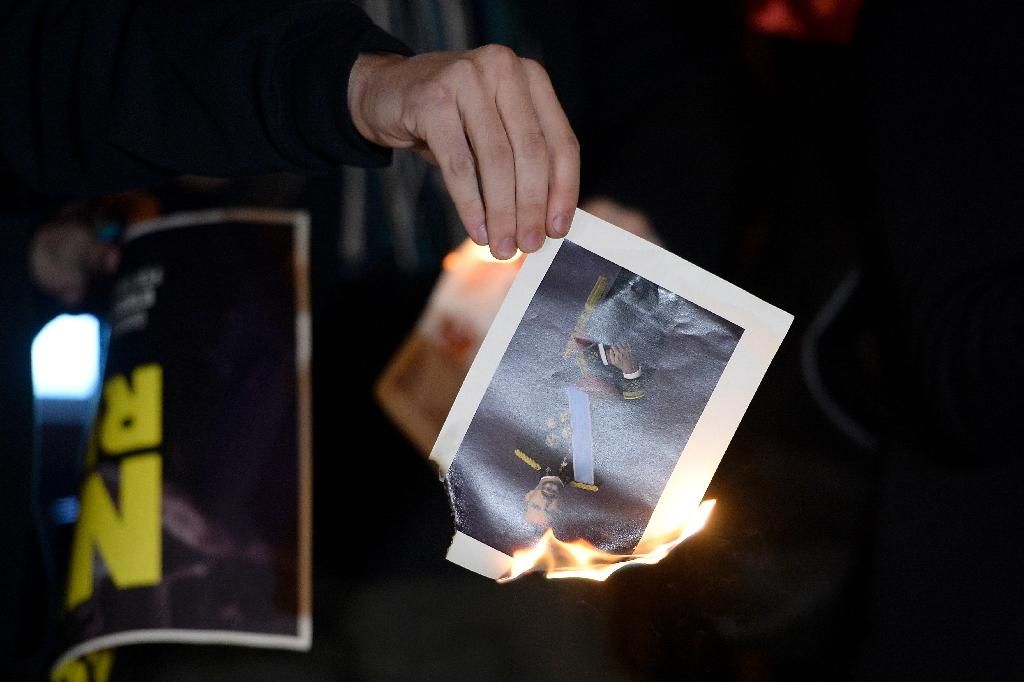A member of radical left-wing Catalan independentist political party CUP burns a picture of Spain's King Felipe on December 12, 2016