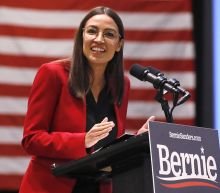 AOC and Michael Moore urge Iowa voters not to 'play it safe' as they stand in for Sanders
