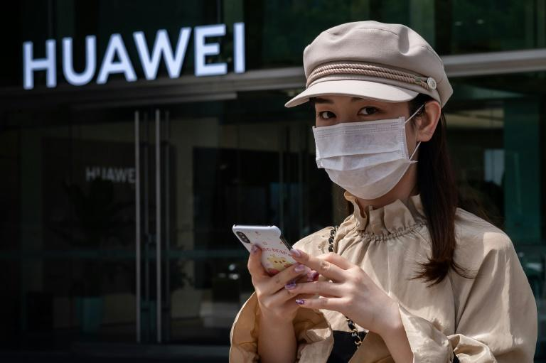 A woman in Beijing walks in May 2020 past a shop of Huawei, the Chinese telecom giant increasingly targeted by the United States (AFP Photo/NICOLAS ASFOURI)