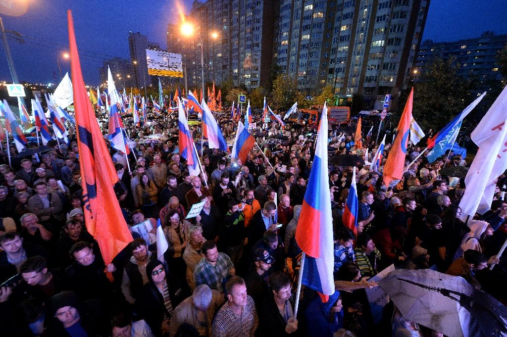 Russia's opposition supporters hold flags during a rally in Lyublino, a suburb of Moscow on September 20, 2015