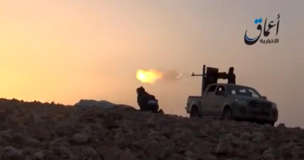 An image grab taken from a video uploaded on October 10, 2014, by Aamaq News Agency allegedly shows Islamic State group fighters firing from an armed vehicle on the outskirts of Ain al-Arab, Syria, on the border with Turkey (AFP Photo/)