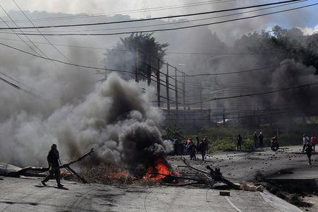 A supporter of Salvador Nasralla, presidential candidate for the Opposition Alliance Against the Dictatorship, walks by a burning barricade settled to block road during a protest caused by the delayed vote count for the presidential election in Tegucigalpa, Honduras December 1, 2017. REUTERS/Jorge Cabrera