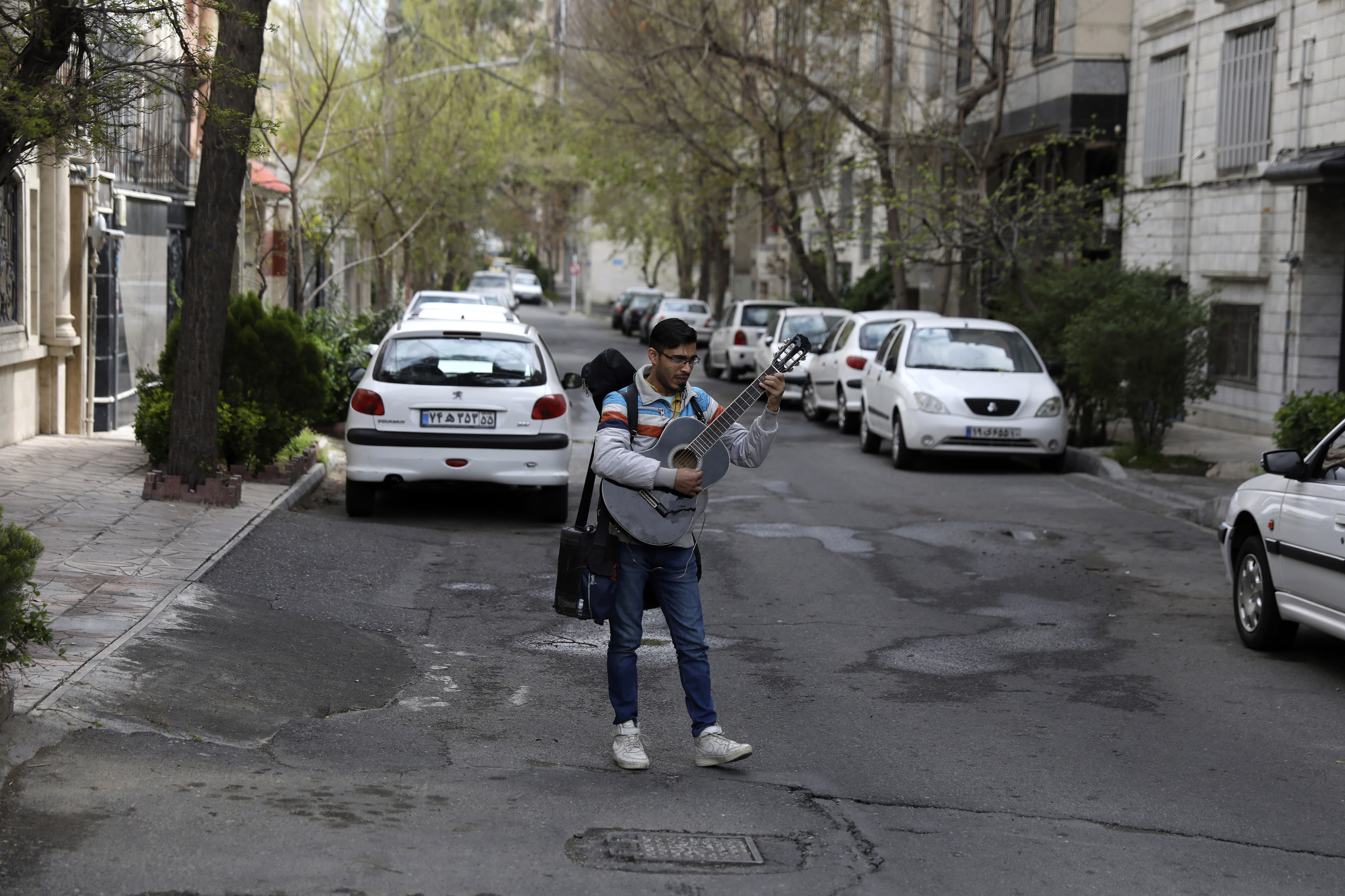 A street musician sings and plays music in an empty street in Tehran, Iran, Thursday, March 26, 2020. Iran is battling the worst new coronavirus outbreak in the region and authorities have advised people to stay at home and trying to enforce new policy imposing the kinds of lockdowns when the country spending the new year holidays. (AP Photo/Vahid Salemi)