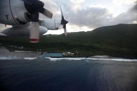 A U.S. Coast Guard C-130 loaded with relief supplies and disaster management personell flies over the island of American Samoa.