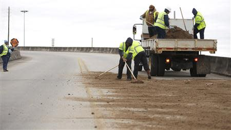 Workers with the city of Mobile shovel dirt on a bridge as cold weather descends on Mobile, Alabama January 28, 2014. REUTERS/Lyle Ratliff