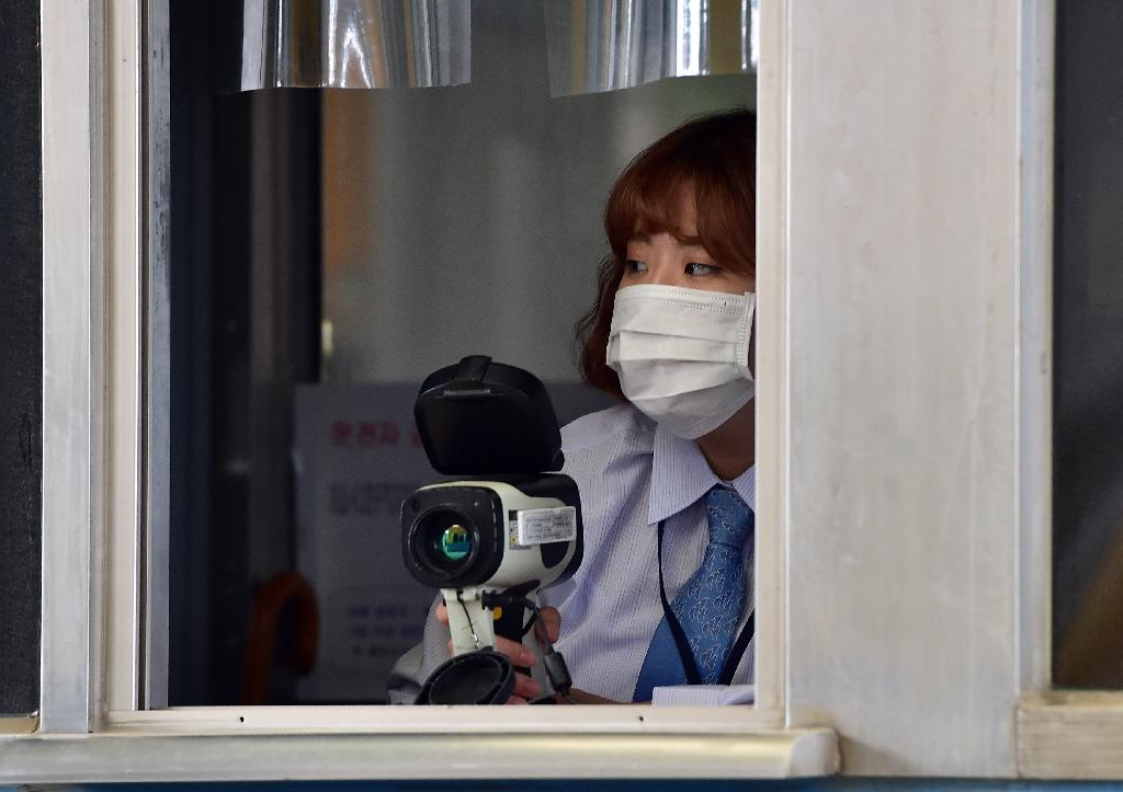 An official checks the body heat of South Korean workers arriving from North Korea's Kaesong Industrial Complex, at the customs gate of the inter-Korean transit office in Paju, on June 13, 2015 (AFP Photo/Jung Yeon-Je)