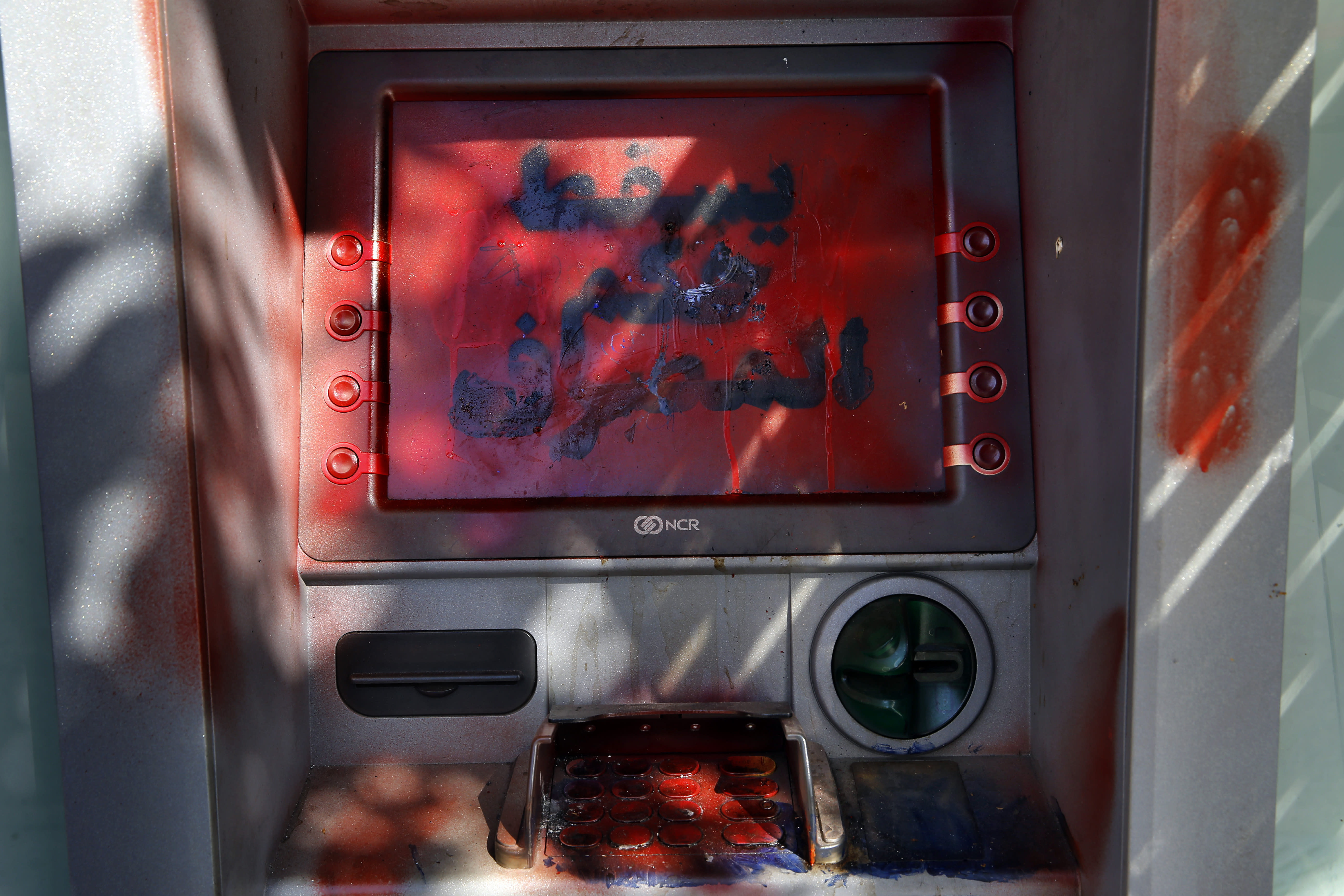 """A damaged ATM screen has been spray painted with a message that reads in Arabic, """"Down with the rule of the banks,"""" in Beirut, Lebanon, Tuesday, Nov. 12, 2019. Lebanon's banking association says banks will stay closed due to a strike by employees, as country's financial crisis worsens. (AP Photo/Bilal Hussein)"""