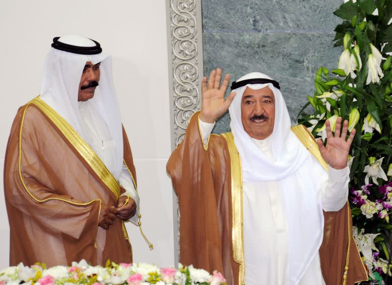 FILE PHOTO: Kuwait's Emir Sheikh Sabah waves at the start of the forth session of the 13th term of the parliament as Crown Prince Sheikh Nawaf stands to his side