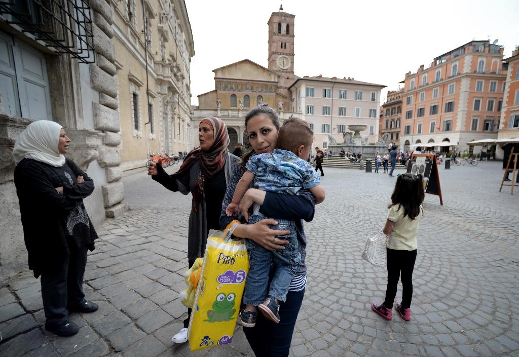 Nour, 30, a Syrian refugee and one of the 12 Syrian asylum seekers Pope Francis brought back with him from Greek island of Lesbos, holds her son Riad, 2, as she arrives at the St. Egidio Roman Catholic Charity in Rome on April 18, 2016 (AFP Photo/Filippo Monteforte)