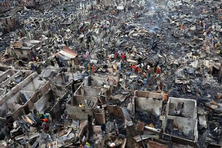 Slum dwellers are seen searching for their belongings from ashes after fire broke out on their shelters in Dhaka