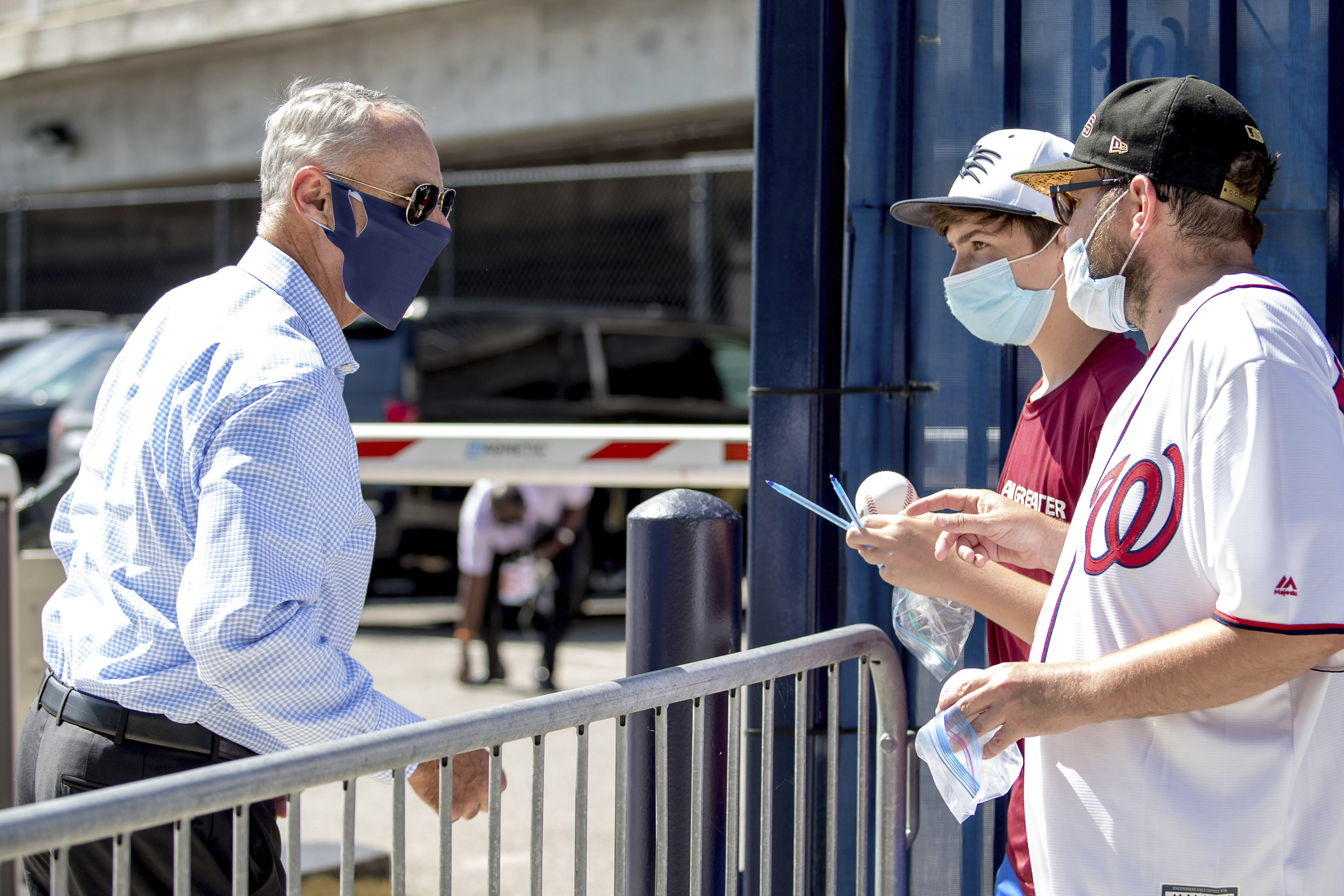 MLB Commissioner Rob Manfred, left, speaks with fans as he arrives at Nationals Park for the New York Yankees and the Washington Nationals opening day baseball game, Thursday, July 23, 2020, in Washington. (AP Photo/Andrew Harnik)