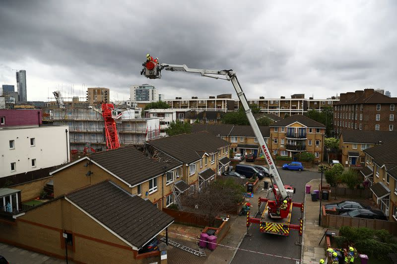 Rescue personnel work at the area where a crane collapsed in Bow, east London