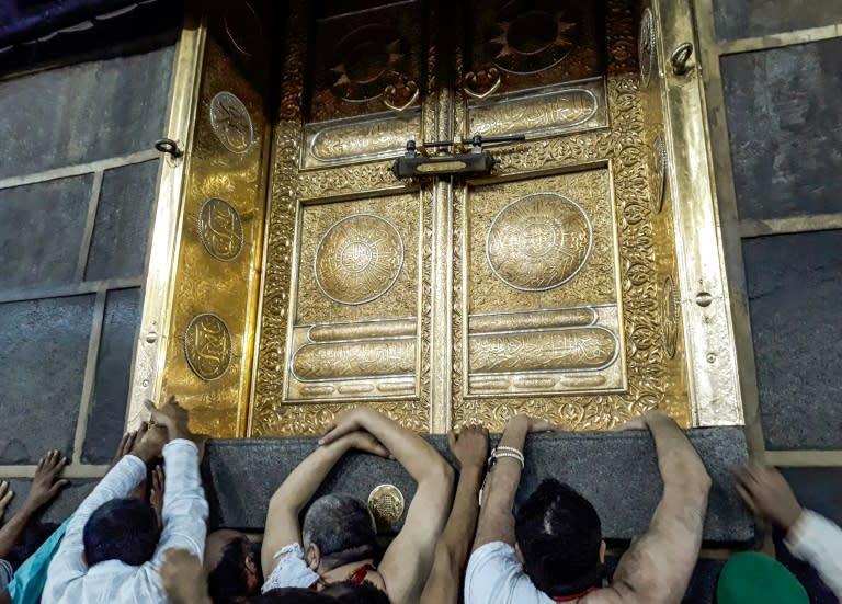 Muslims pilgrims gather outside the door of the Kaaba, Islam's holiest shrine, in Mecca, Saudi Arabia