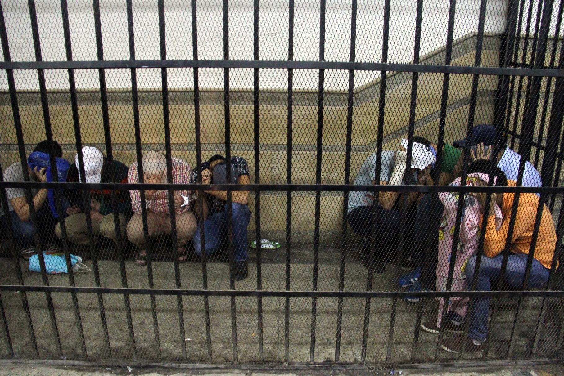 Eight Egyptian men on trial for doing a video prosecutors claimed was of a gay wedding hide their identities as they sit in the defendents' cage during their trial in Cairo on November 1, 2014 (AFP Photo/)