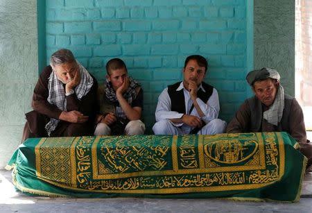 Afghans sit beside the coffin of Afghan journalist Zabihullah Tamanna, before a burial ceremony, in Kabul, Afghanistan June 7, 2016. REUTERS/Omar Sobhani