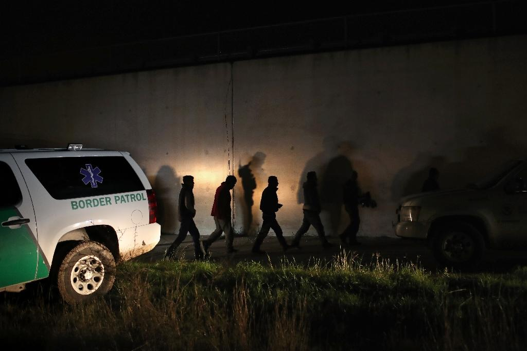 Captured undocumented immigrants walk past a stretch of border levee wall while being taken into custody by Border Patrol agents on February 22, 2018 near McAllen, Texas (AFP Photo/JOHN MOORE)