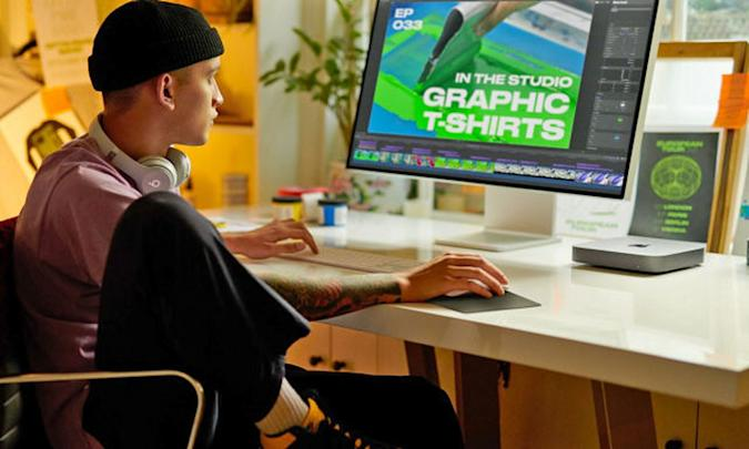 A graphic designer sits at their desk with a Mac Mini clearly visible on the desk top.