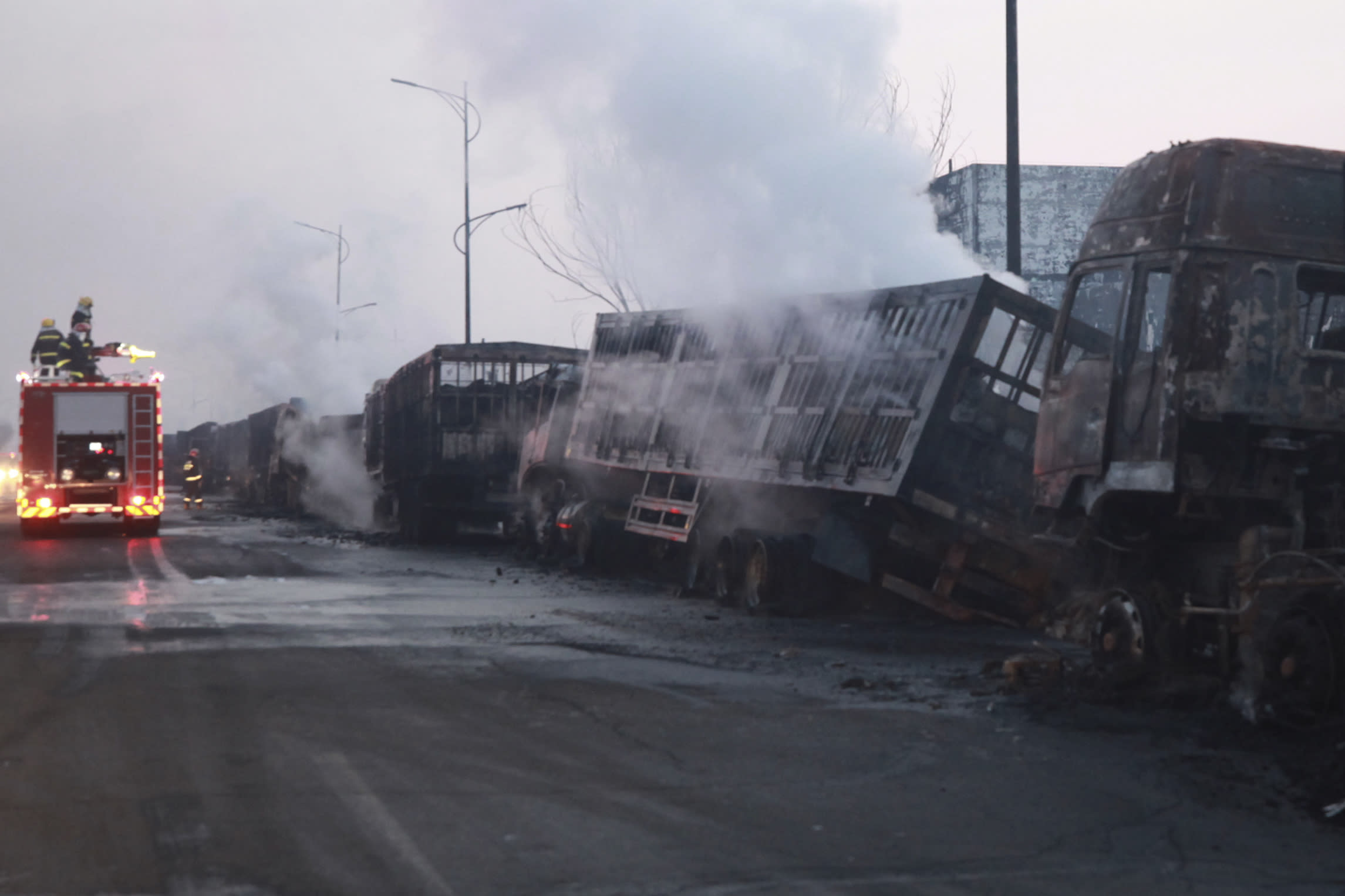 In this photo released by Xinhua News Agency, firefighters try to extinguish burning vehicles in the aftermath of an explosion at a plant operated by the Hebei Shenghua Chemical Industry Co. Ltd that destroyed dozens of vehicles nearby on Wednesday, Nov. 28, 2018 in Zhangjiakou city, northeastern China's Hebei province.(Xinhua via AP)