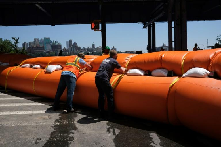 Workers erect temporary flood barriers in the South Street Seaport neighborhood in New York City (AFP Photo/SPENCER PLATT)