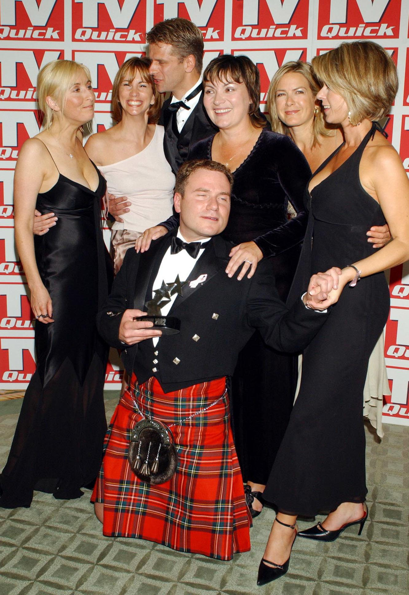 GMTV presenters with their award at the TV Quick Awards at the Dorchester Hotel in London. (L-R) Fiona Phillips, Andrea McLean, Andrew Castle, Richard Arnold (on floor), Lorraine Kelly Penny Smith, and Kate Garraway.