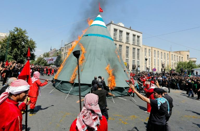 Iranian and Iraqi Shiite Muslims burn a tent during the re-enactment of events of the 10th day of the month of Muharram which marks the peak of Ashura, in the Iranian capital Tehran
