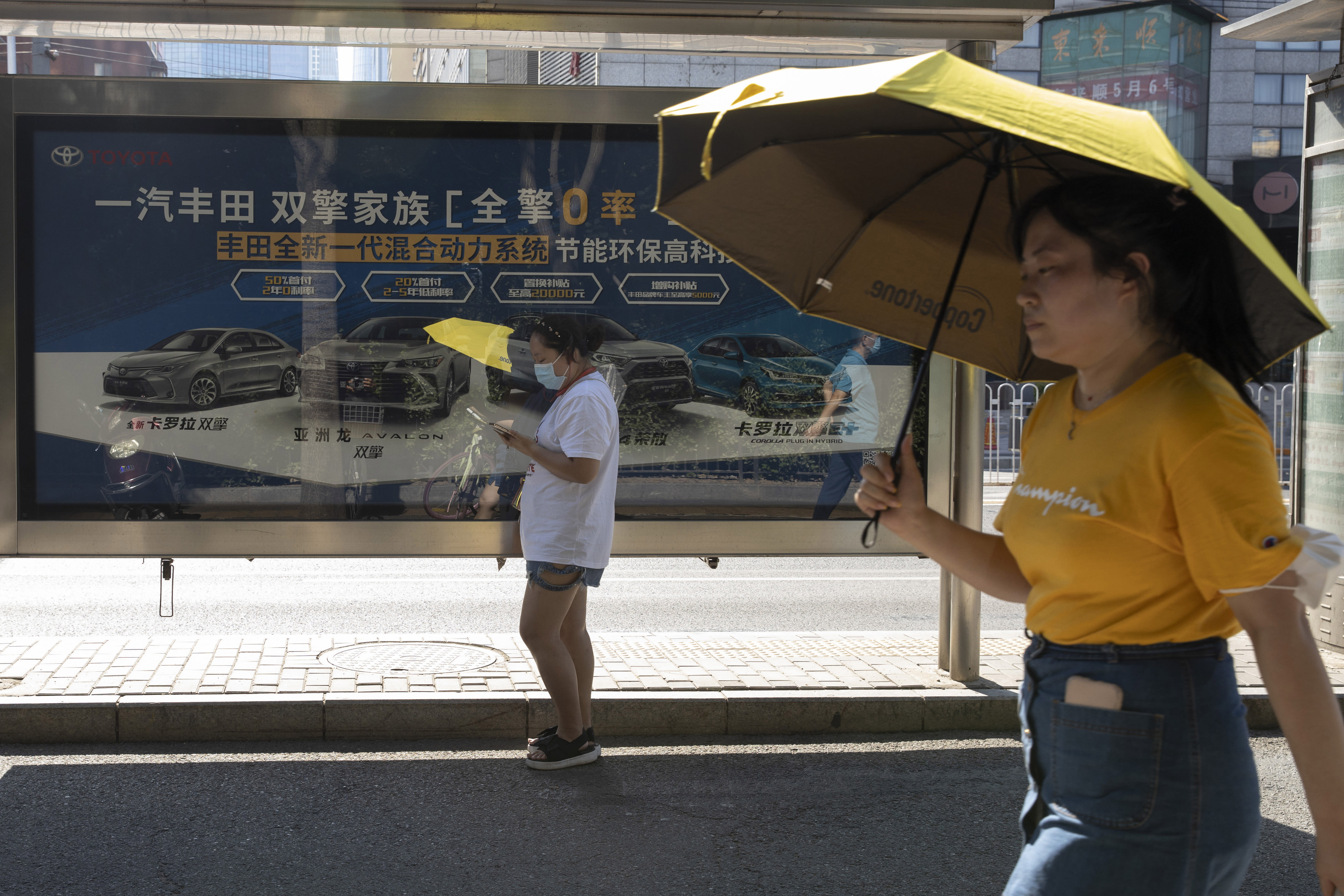 Residents pass by an advertisement for Hybrid cars from Toyota on the streets of Beijing on Tuesday, Aug. 4, 2020. China's auto sales rose by 16.4% in July over a year earlier to 2.1 million units in a sign of sustained recovery for the industry's biggest global market, an industry group said Tuesday. (AP Photo/Ng Han Guan)