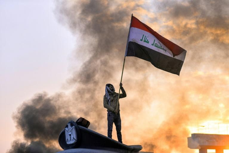 An anti-government protester waves the national flag from above a statue of a policeman's hat during a demonstration in the central Iraqi city of Najaf