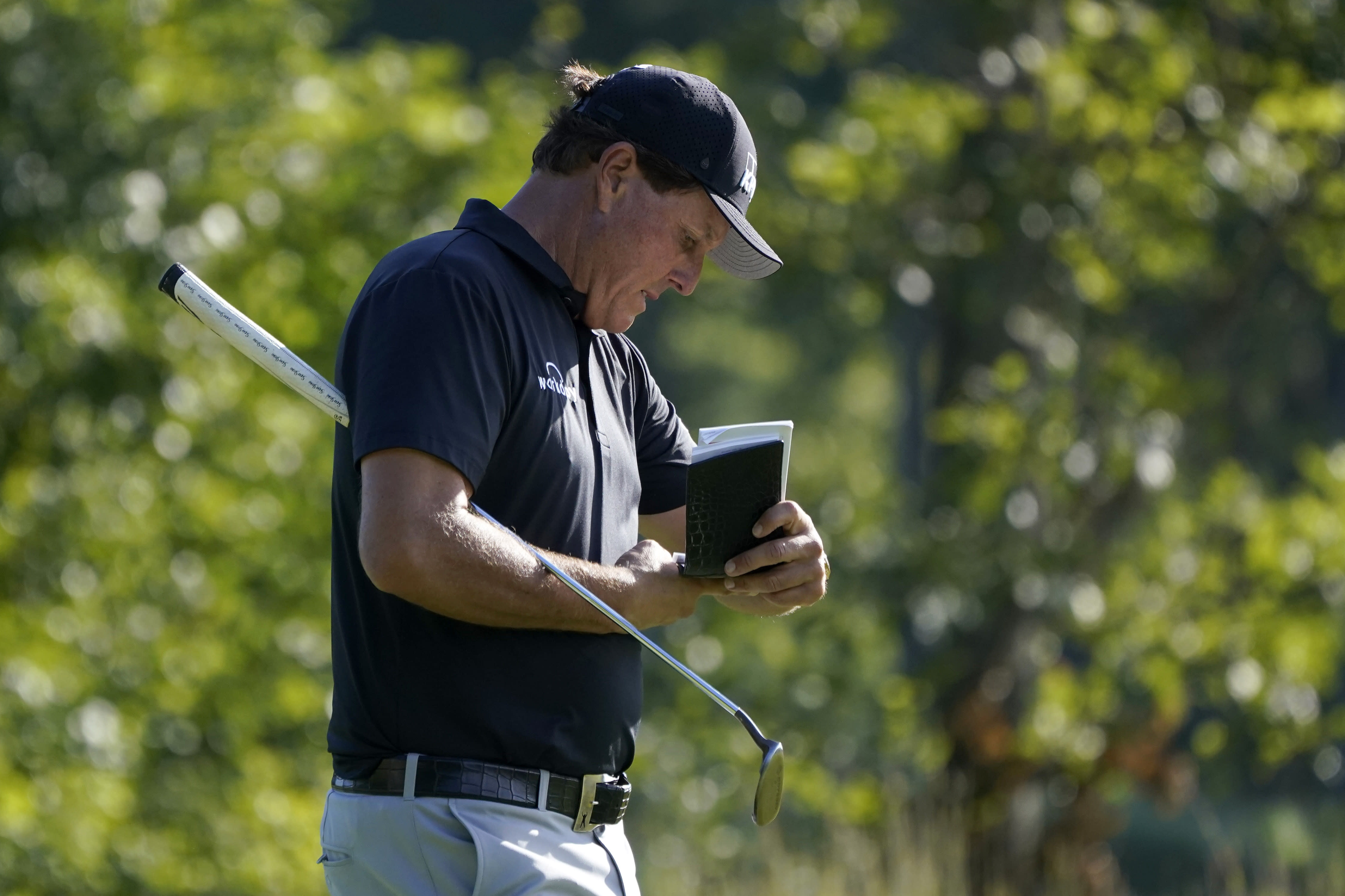 Phil Mickelson refers to his notes as he walks up onto the 14th green during the second round of the Northern Trust golf tournament at TPC Boston, Friday, Aug. 21, 2020, in Norton, Mass. (AP Photo/Charles Krupa)
