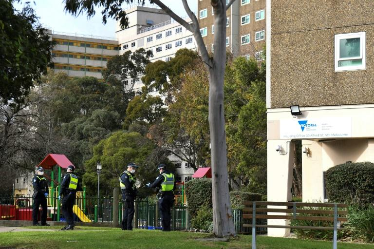Police stand guard outside a public housing estate locked down in Melbourne due to a spike in coronavirus cases (AFP Photo/William WEST)