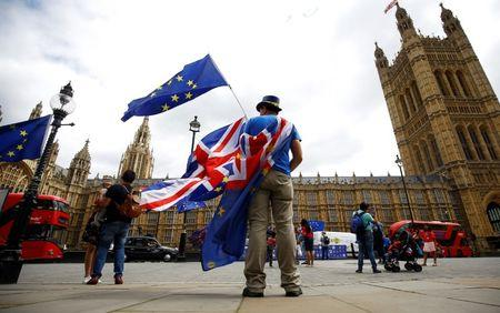 FILE PHOTO: Anti-Brexit demonstrators wave EU and Union flags opposite the Houses of Parliament, in London, Britain, June 19, 2018. REUTERS/Henry Nicholls/File Photo