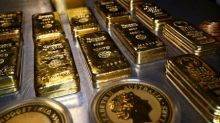 Gold up on soft dollar, set for first weekly gain in four