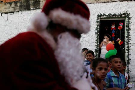 Santa Claus walks during a visit to residents of the slum of Petare in Caracas, Venezuela. REUTERS/Ueslei Marcelino