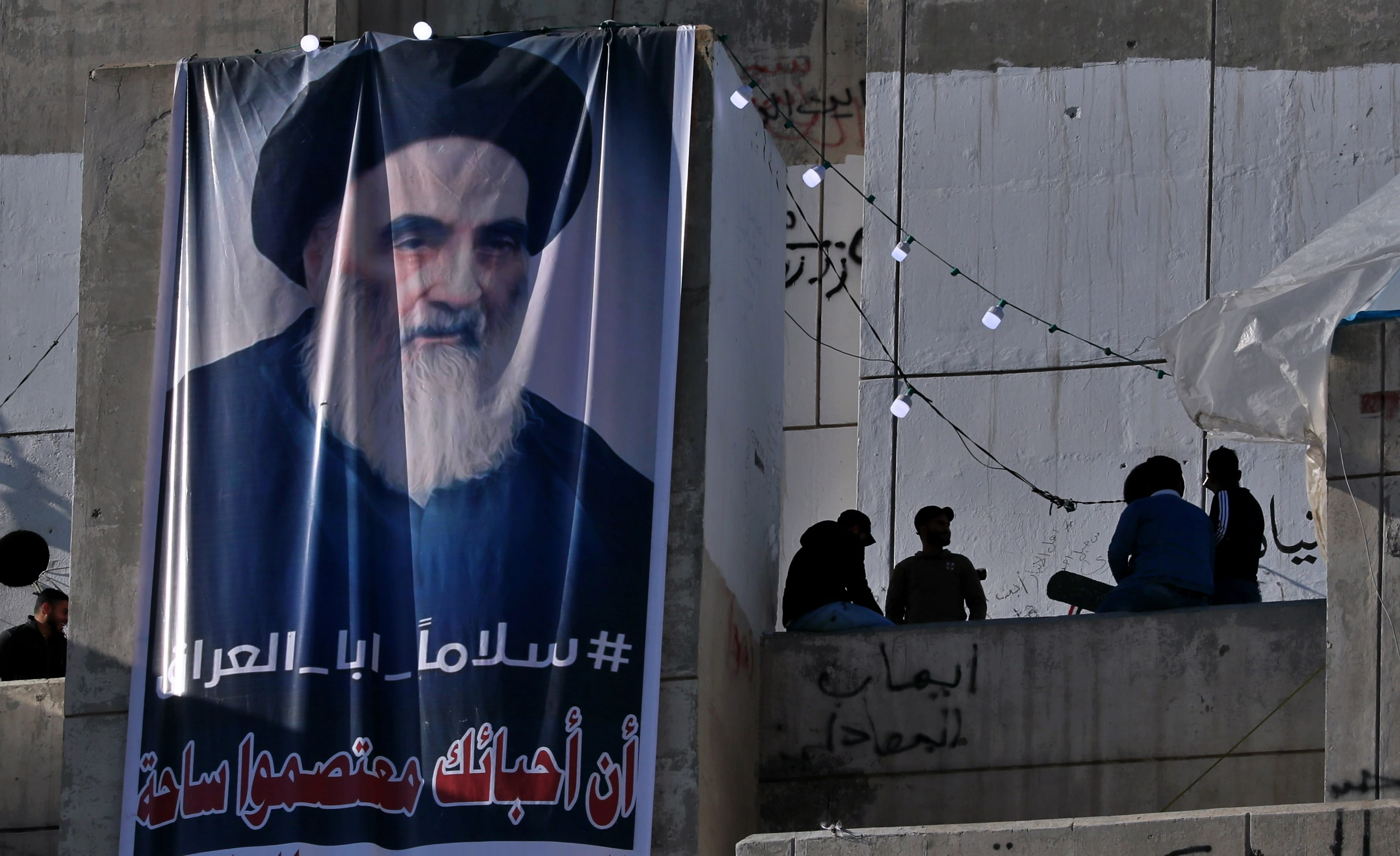 """In this Saturday, Feb. 1, 2020 photo, a poster of Grand Ayatollah Ali al-Sistani is on display with Arabic that reads, """"Peace, father of Iraq,"""" in Tahrir Square, Baghdad, Iraq. Al-Sistani, Iraq's top Shiite cleric, turns 90 this year, and when he recently had surgery it sent chills around the country and beyond. What happens when al-Sistani is gone? Iran is likely to try to exploit the void to gain followers among Iraq's Shiites. Standing in its way is the Hawza, the centuries-old institution of religious learning which al-Sistani heads and which follows its own tradition-bound rules. (AP Photo/Khalid Mohammed)"""