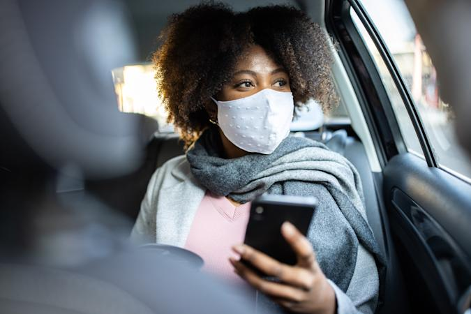 Mixed race woman with protective face mask travel by taxi. Businesswoman traveling by taxi during COVID-19 pandemic.