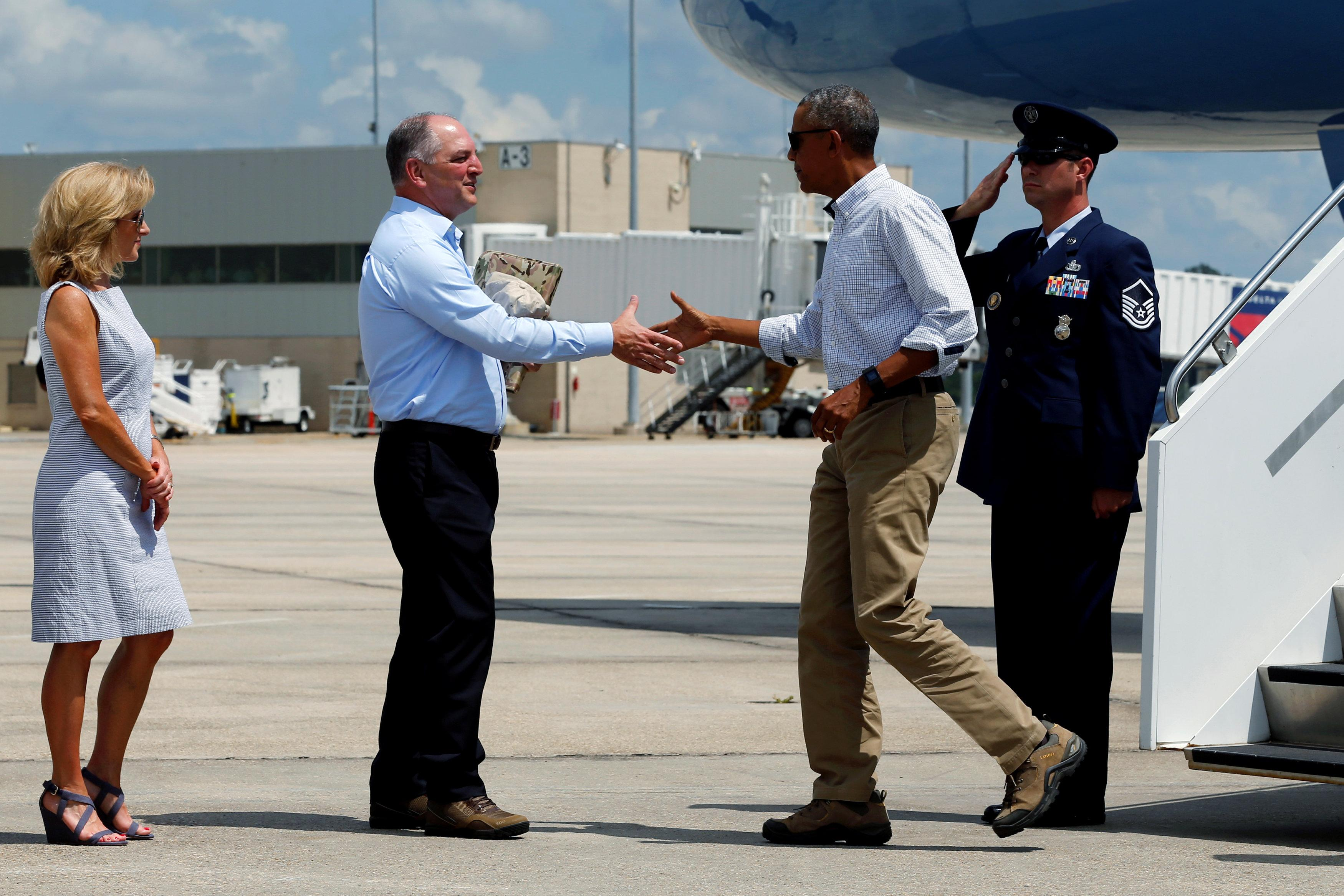 Louisiana Governor John Bel Edwards (2nd L) and his wife Donna (L) greet U.S. President Barack Obama as he arrives aboard Air Force One at Baton Rouge Metropolitan Airport in Baton Rouge, Louisiana, U.S., August 23, 2016. REUTERS/Jonathan Ernst
