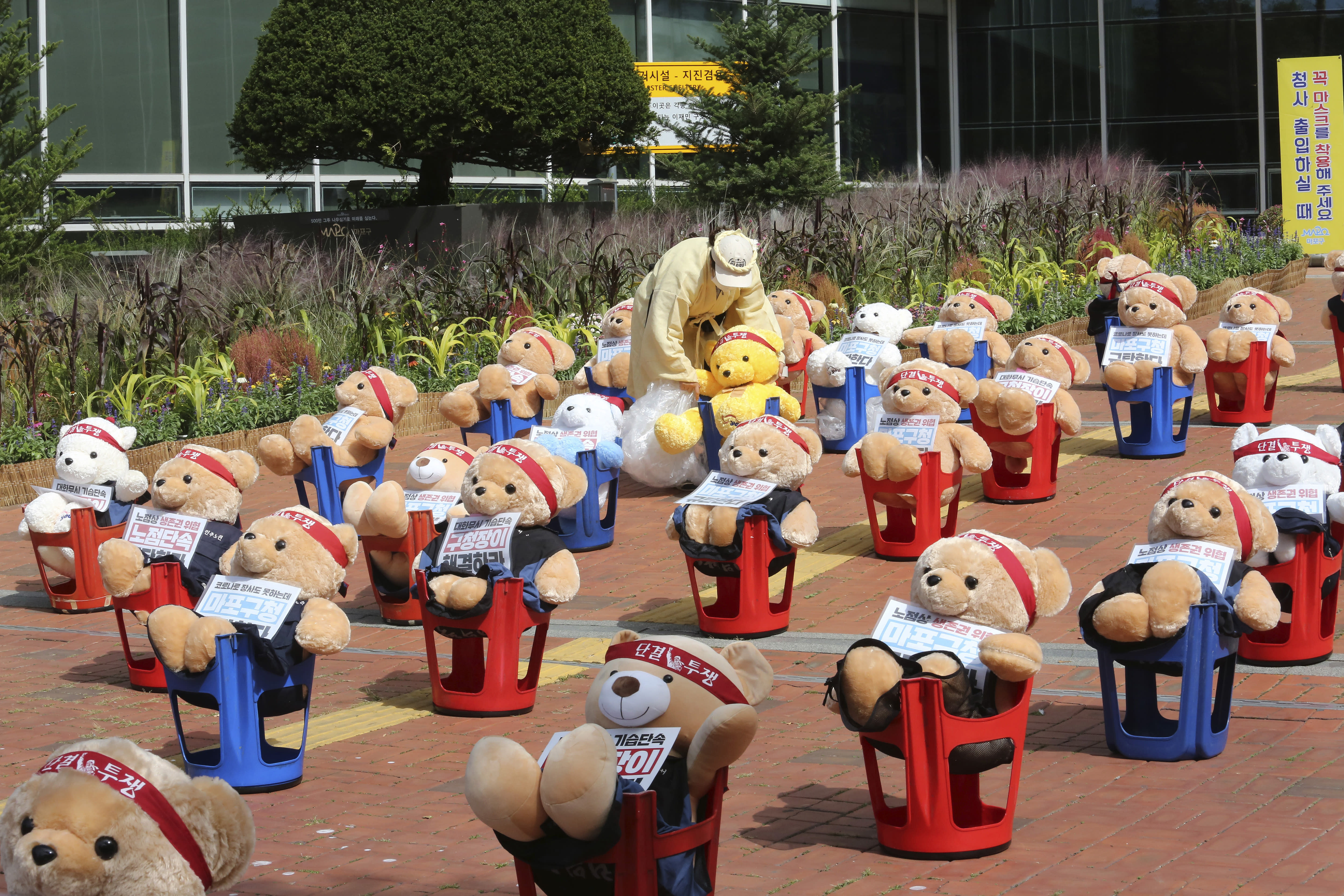 """A street vendor places a teddy bear to protest against a crackdown on illegal street vendors, in front of the Mapo ward office in Seoul, South Korea, Thursday, Sept. 24, 2020. Street vendors replaced protestors with teddy bears to avoid the violation of an ongoing ban on rallies with more than 10 people amid the coronavirus pandemic. The signs read: """"Stop crackdown."""" (AP Photo/Ahn Young-joon)"""
