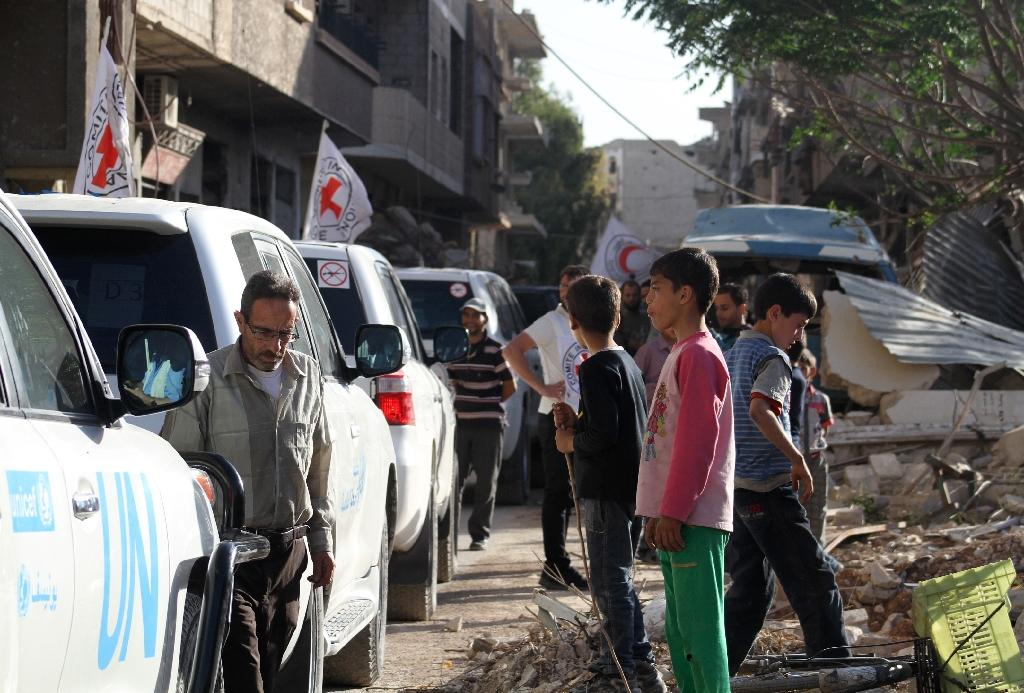 Vehicles of the International Committee of the Red Cross the Syrian Arab Red Crescent and the United Nations wait on a street after an aid convoy entered the rebel-held Syrian town of Daraya, southwest of the capital Damascus, on June 1, 2016